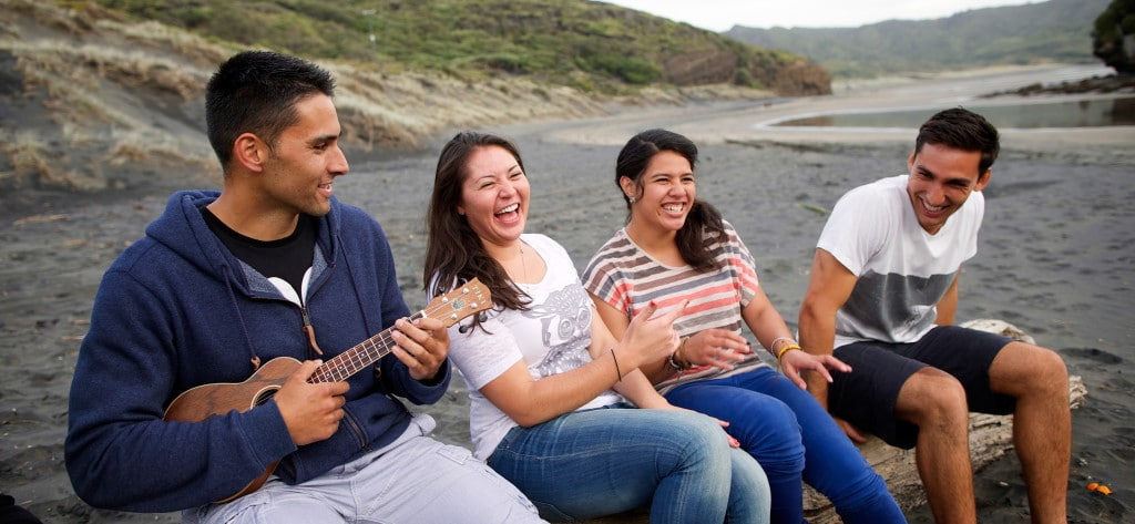 young people enjoy music on the beach